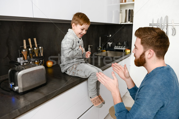 Cheerful father playing with his little cute son in kitchen Stock photo © deandrobot