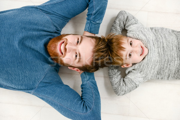 Young bearded father lies on floor with his cheerful son Stock photo © deandrobot
