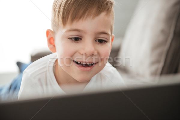 Smiling boy using laptop computer while lies on sofa Stock photo © deandrobot