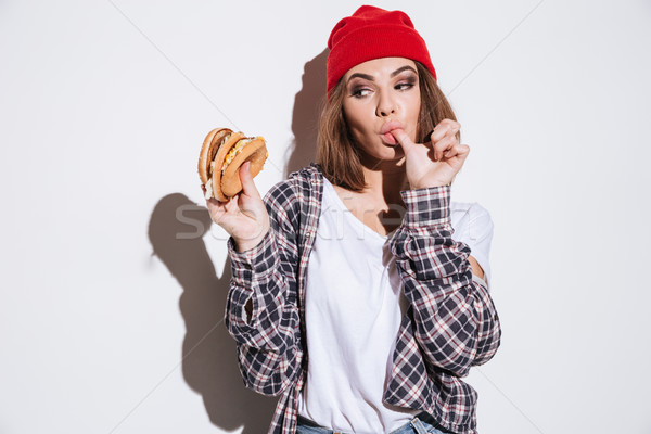 Hungry young lady eating burger Stock photo © deandrobot
