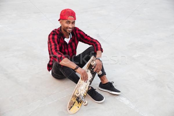 Happy dark skinned young man sitting near his skateboard Stock photo © deandrobot