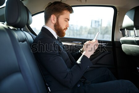 Side view of serious bearded business man holding smartphone Stock photo © deandrobot