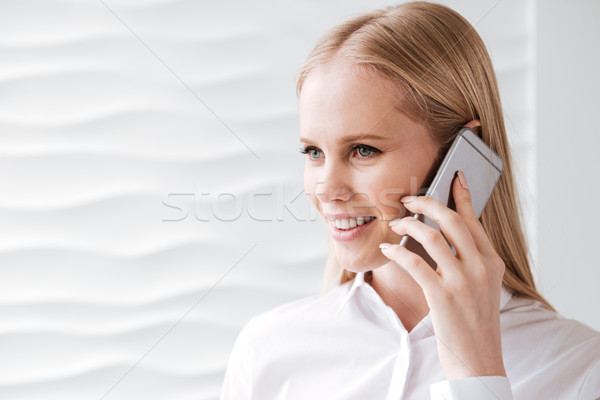 Cheerful young business woman in office talking by phone Stock photo © deandrobot
