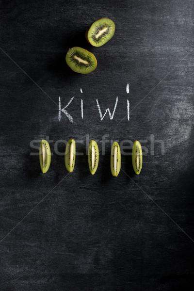 Kiwi over dark chalkboard background Stock photo © deandrobot