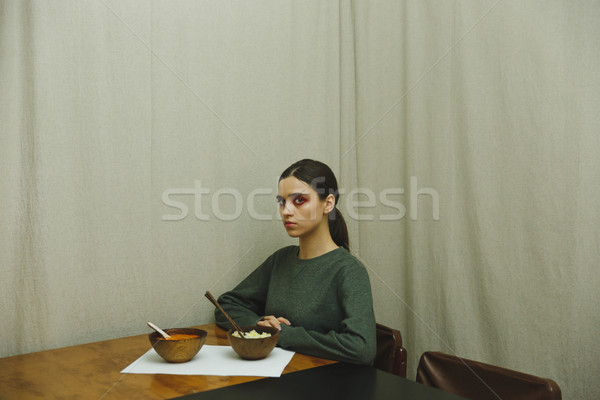 Side view of woman eating by the table Stock photo © deandrobot