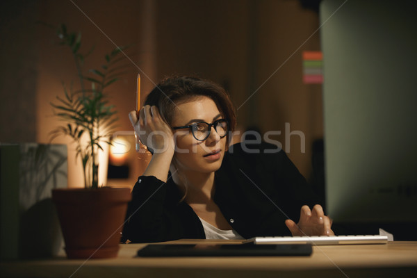 Serious young lady designer using computer Stock photo © deandrobot