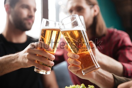 Young men toasting with beer while sitting in pub together Stock photo © deandrobot