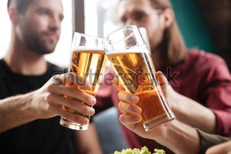 Jonge mannen bier vergadering pub samen Stockfoto © deandrobot
