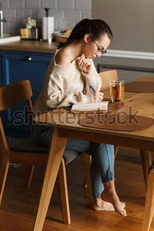 Girl using mobile phone while sitting at the cafe table Stock photo © deandrobot