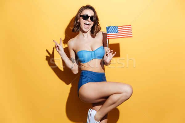 Smiling young woman in swimwear holding USA flag Stock photo © deandrobot
