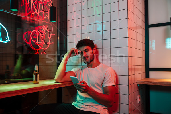 Caucasian young serious man sitting in cafe looking aside Stock photo © deandrobot
