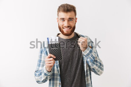 Smiling bearded man in checkered shirt puts money in pocket Stock photo © deandrobot