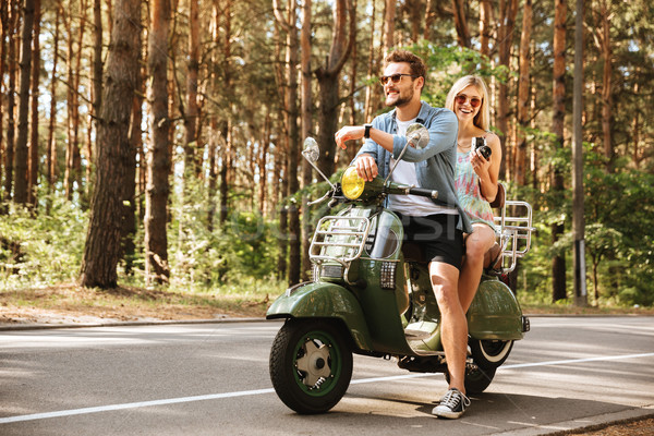 Young handsome man on scooter with girlfriend holding camera Stock photo © deandrobot