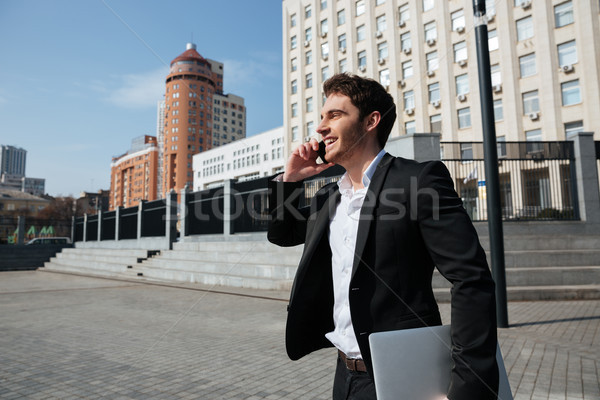 Stock photo: Happy young businessman walking outdoors talking by phone.