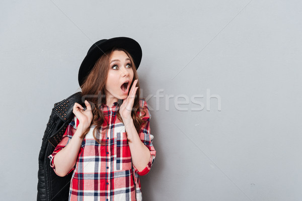 Portrait of an astonished amazed girl in plaid shirt Stock photo © deandrobot