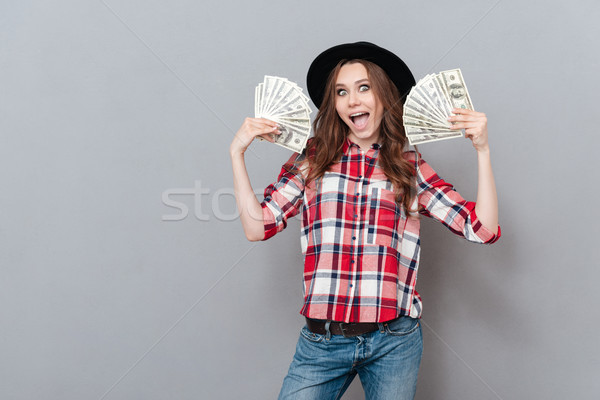 Portrait of a happy excited girl holding money banknotes Stock photo © deandrobot