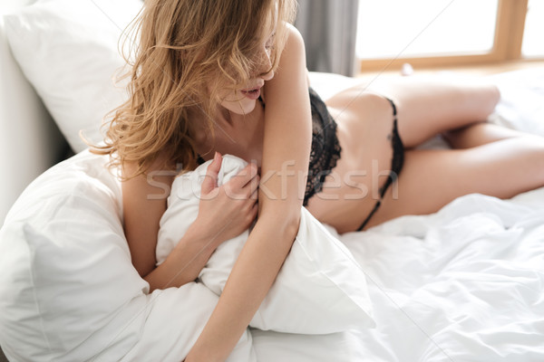 Pretty brunette sexy woman lies on bed Stock photo © deandrobot