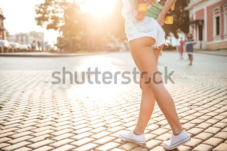Lady with skateboard walking outdoors. Stock photo © deandrobot