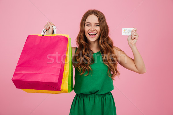 Portrait of a cheerful pretty woman showing shopping bags Stock photo © deandrobot