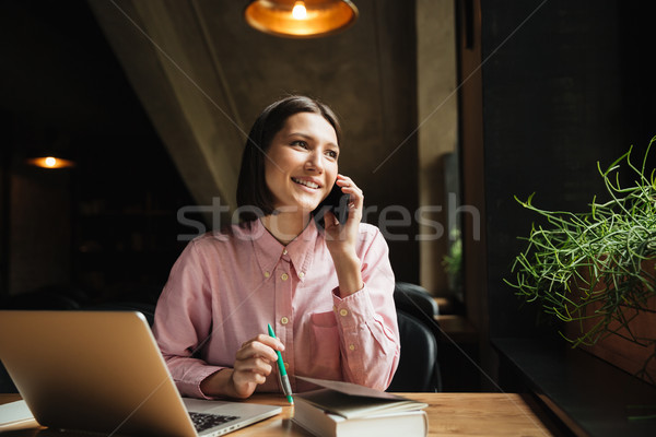 Smiling brunette woman sitting by the table with laptop computer Stock photo © deandrobot