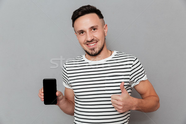 Smiling young man showing display of mobile phone Stock photo © deandrobot