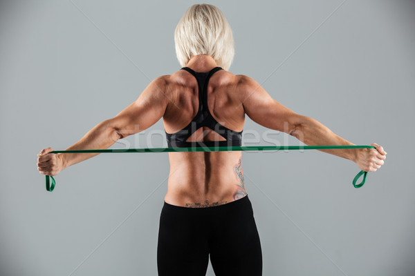 Back view portrait of a strong muscular adult sportswoman Stock photo © deandrobot