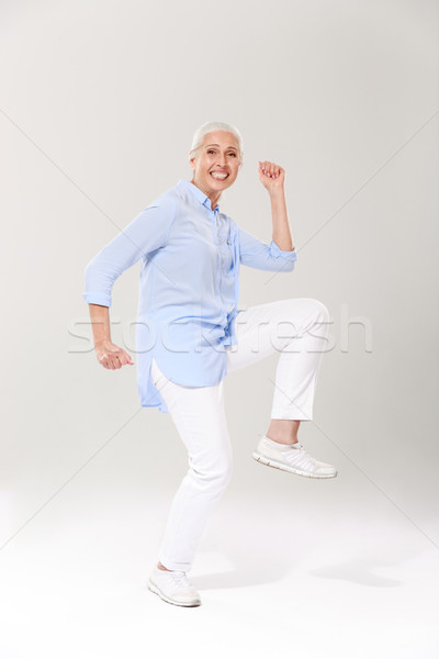 Full-length photo of playful old lady, having fun over white bac Stock photo © deandrobot