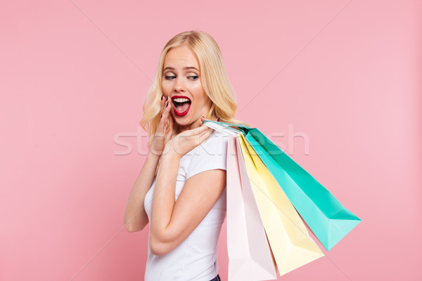 Side view of surprised blonde woman holding packages on shoulder Stock photo © deandrobot