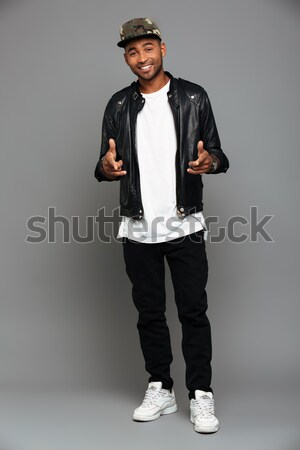 Full length photo of stylish afro american man pointing with two Stock photo © deandrobot