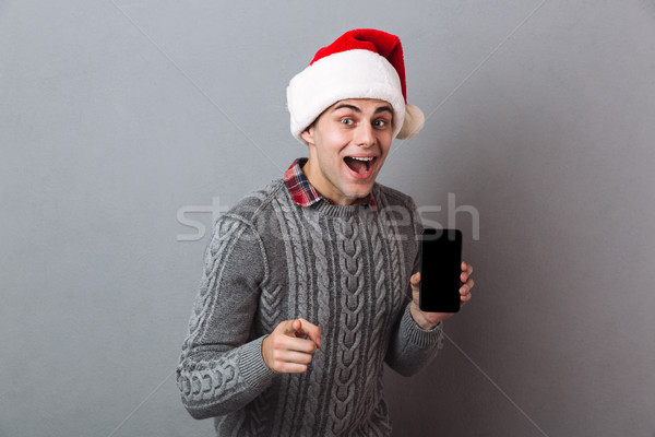 Excited happy emotional man showing display of mobile phone. Stock photo © deandrobot