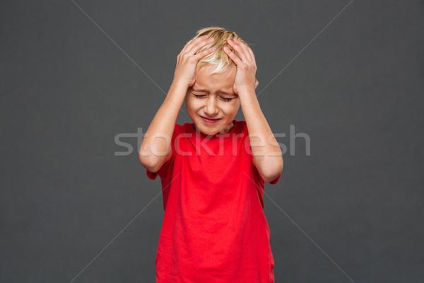 Triste pequeno menino criança dor de cabeça foto Foto stock © deandrobot