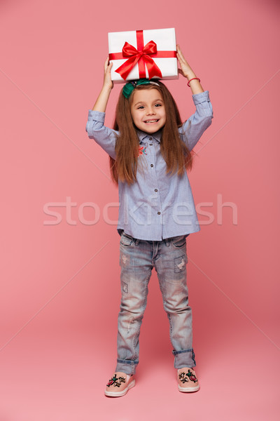 Full-length portrait of joyous female kid holding gift box with  Stock photo © deandrobot