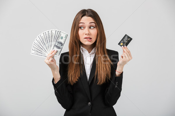 Pensive disappointed lady holding cash and credit card isolated Stock photo © deandrobot