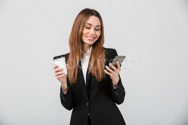 Handsome delightful lady using smartphone and holding coffee isolated Stock photo © deandrobot
