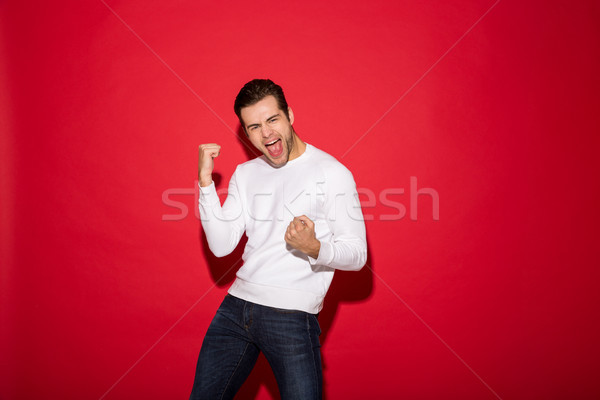 Happy screaming man in sweater rejoice and looking at camera Stock photo © deandrobot