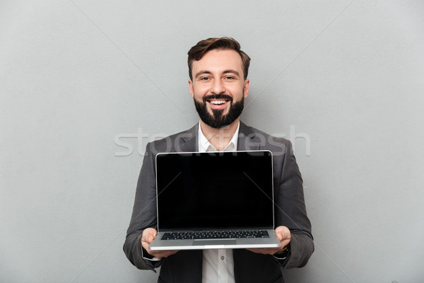 Picture of smiling bearded man holding silver personal computer  Stock photo © deandrobot
