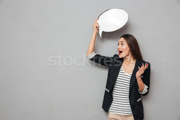 Shocked asian business woman holding blank speech bubble overhead Stock photo © deandrobot