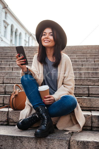 Portrait of a cheery smiling woman texting on mobile phone Stock photo © deandrobot