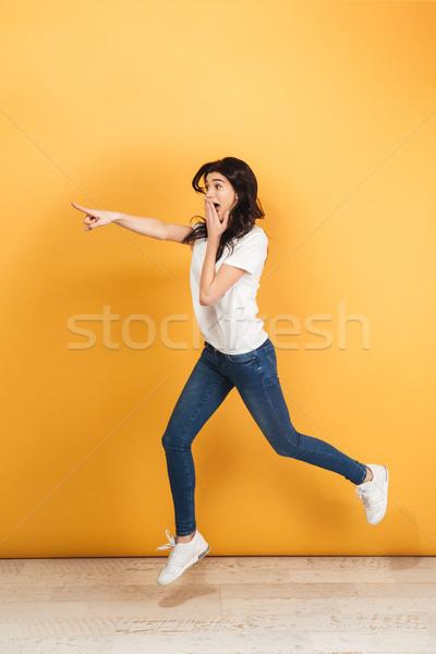 Geschokt vrouw springen wijzend afbeelding jonge Stockfoto © deandrobot