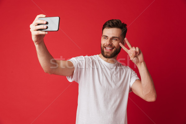 Young man standing isolated make selfie by mobile phone make peace gesture. Stock photo © deandrobot