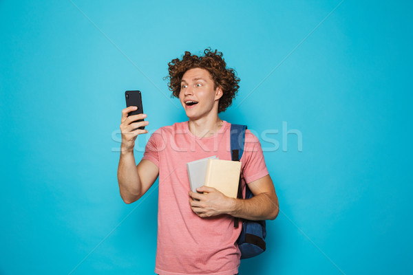 Image of attractive youngster guy with curly hair wearing casual Stock photo © deandrobot