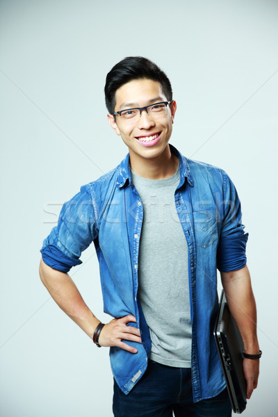 Portrait of a young smiling asian man holding laptop on gray background Stock photo © deandrobot
