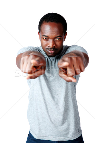Handsome african man pointing at you over white background Stock photo © deandrobot