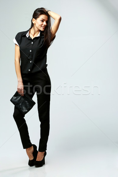 Young happy woman in black formal clothes standing on gray background Stock photo © deandrobot