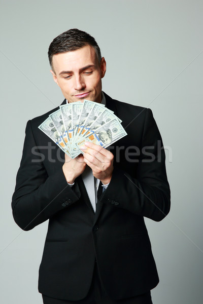 Businessman holding group of dollar bills on a gray background Stock photo © deandrobot