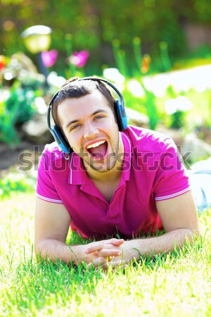 Portrait of a smiling woman lying on green grass Stock photo © deandrobot