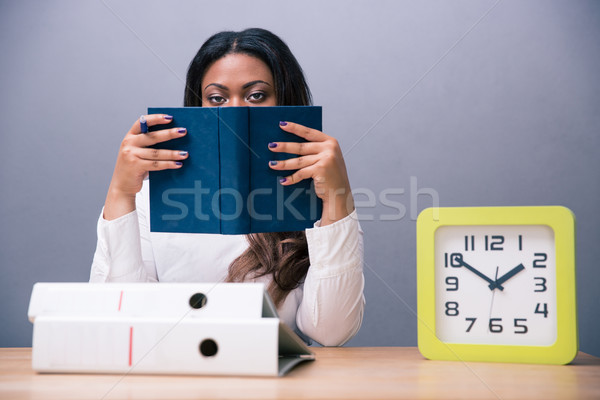 Businesswoman sitting at the table and covering her face with bo Stock photo © deandrobot
