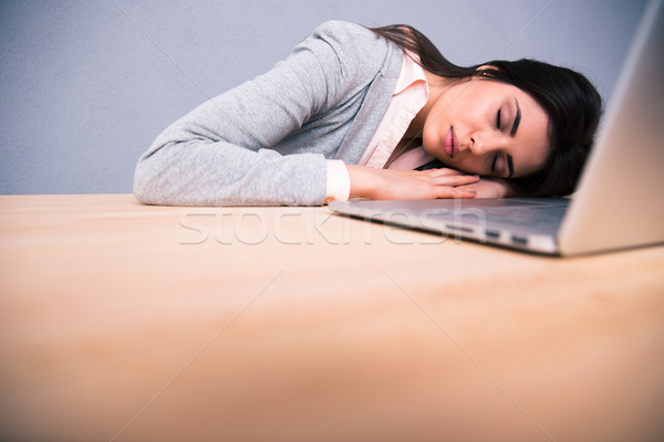 Young pretty woman sleeping on the table Stock photo © deandrobot