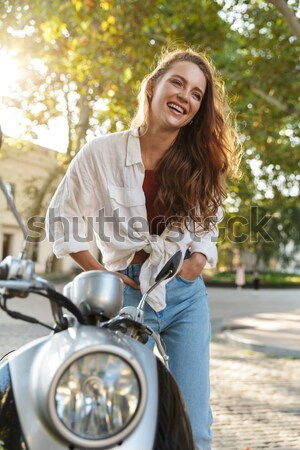 Smiling young woman on a scooter Stock photo © deandrobot
