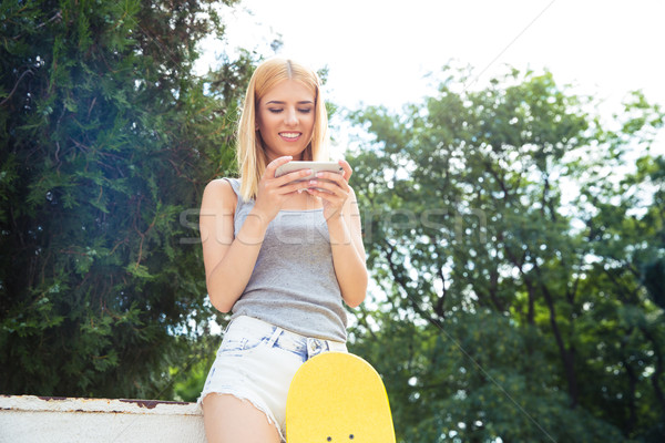 Girl with skateboard using smartphone Stock photo © deandrobot